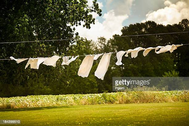 cotton laundry hanging on a clothesline - clothesline stock pictures, royalty-free photos & images