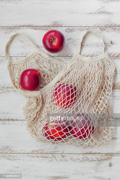 cotton mesh bag reusable containing red apples, against rustic white wood background, close-up. - malla textil fotografías e imágenes de stock