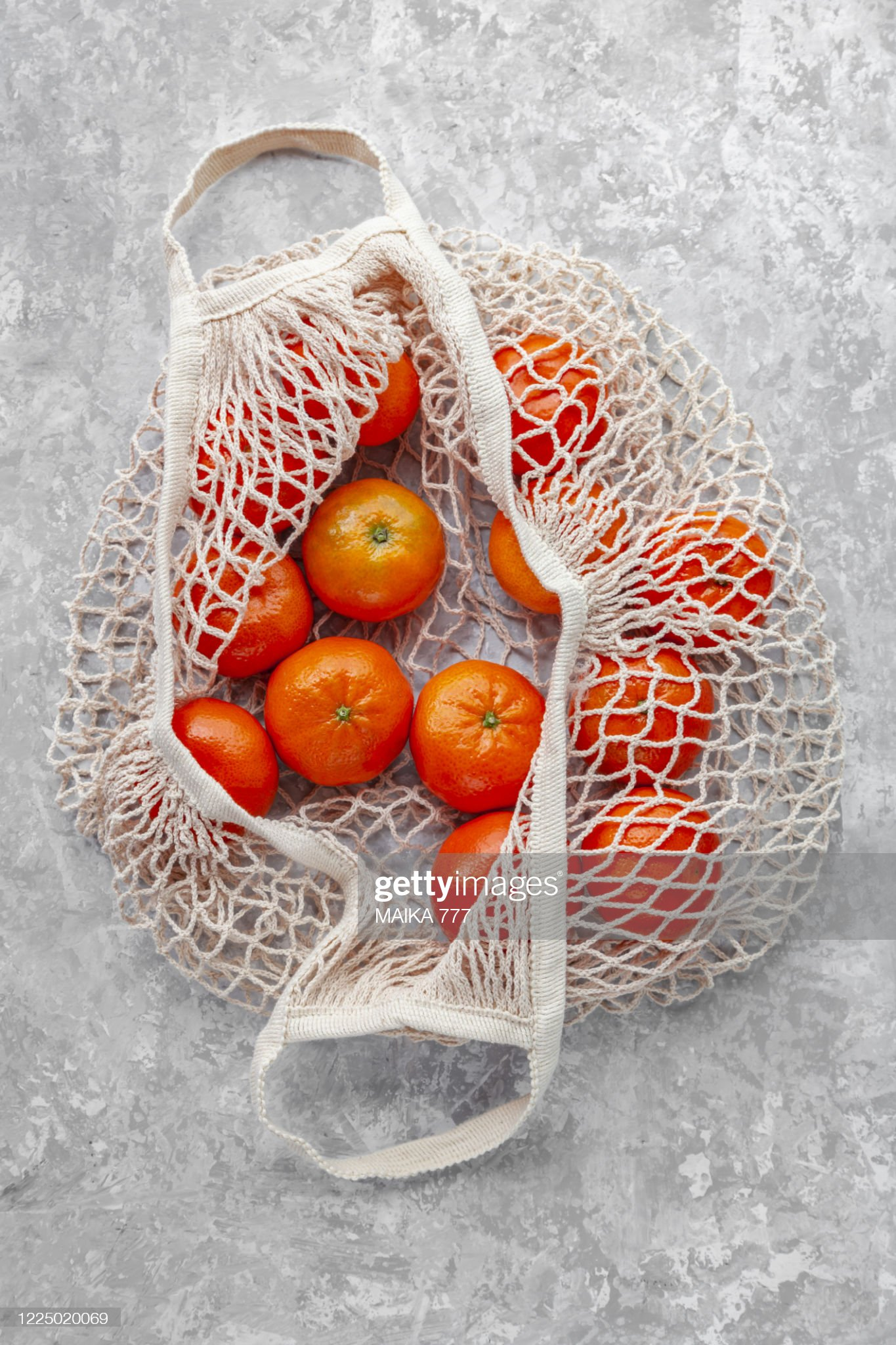 Cotton mesh grocery shopping bag reusable containing tangerines, against gray background, close-up : Stock Photo