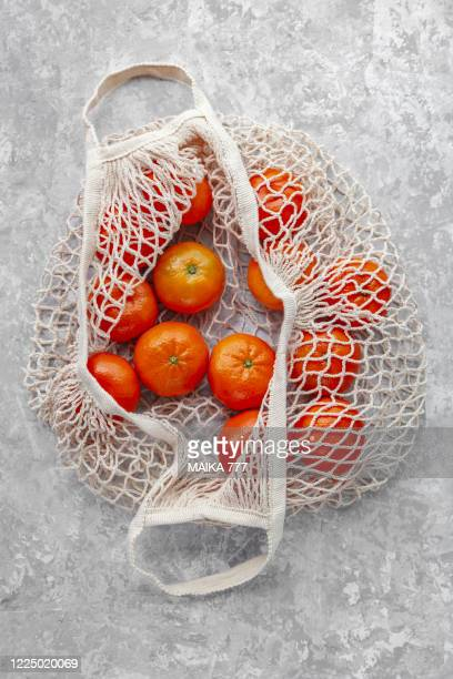 cotton mesh grocery shopping bag reusable containing tangerines, against gray background, close-up - bag stock pictures, royalty-free photos & images
