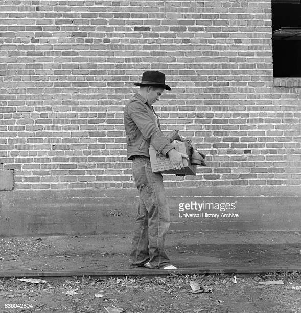 Cotton Picker Carrying Farm Security Administration Grant of Food and Necessities to his Family at FSA Migrant Camp Bakersfield California USA...