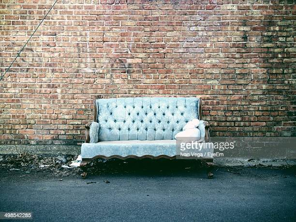 Couch against brick wall on street