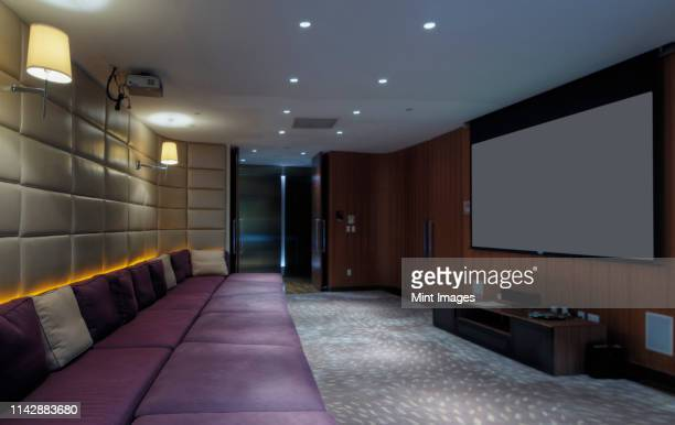 couch and screen in home theater room - entertainment center stock pictures, royalty-free photos & images