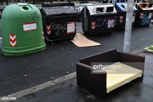 A couch has been abandoned on the sidewalk near waste containers on January 11 2018 in Rome / AFP PHOTO / Alberto PIZZOLI