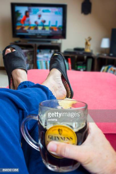 Couch potato lazy man in comfy chair with pint of beer wearing worn slippers with big toes sticking through and watching television in living room