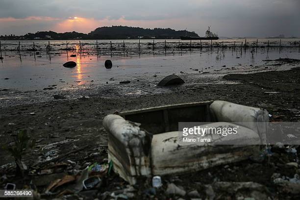 A couch rests among pollution along the edge of Guanabara Bay the venue for the Olympic sailing on August 2 2016 in Niteroi Rio de Janeiro state...