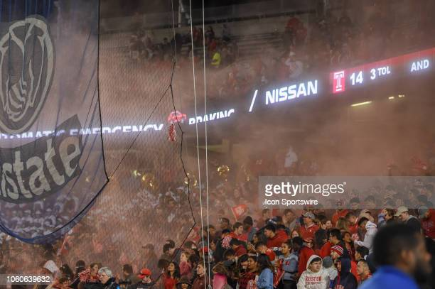 Cougar fans squirt red powder into the air following a first half touchdown during the football game between the Temple Owls and Houston Cougars on...