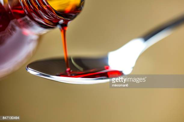 Cough syrup being poured onto spoon. Medical concept