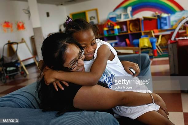 Coulet Johnson, age 9, hugs childcare coordinator Stela Rangel at the Family Gateway family homeless shelter on June 15, 2009 in Dallas, Texas. More...