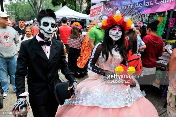 TOPSHOT A coulpe fancy dressed as Catrina take part in the Catrinas Parade along Reforma Avenue in Mexico City on October 26 2019 Mexicans get ready...