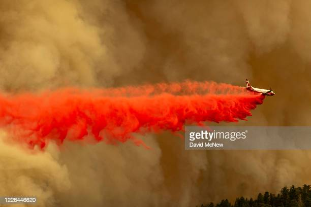 Coulson 737 firefighting tanker jet drops fire retardant to slow Bobcat Fire at the top of a major run up a mountainside in the Angeles National...