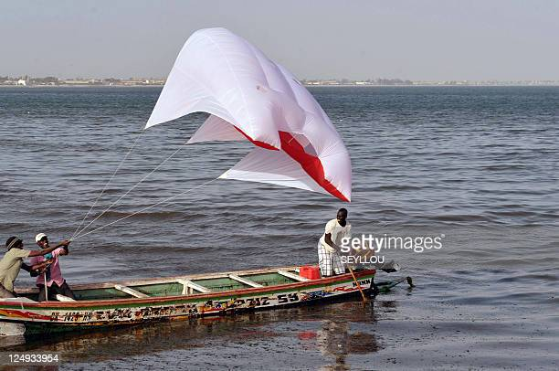 Coumba SYLLA Senegalese men use a kite to pull a canoe on March 23 2011 in Dakar Senegal where fifty fishermen perish at sea each year is testing...