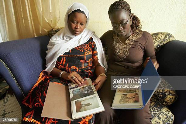 Yacine Mar Diop Diagne and her daughter Coumba go through 05 December 2007 a family photo album in their house with photos of her Diop's husband...