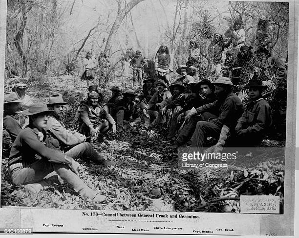 A council between the Apache leader Geronimo and General Crook seated on the ground in a wooded area
