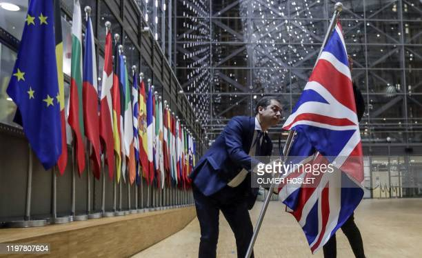 Council staff members remove the United Kingdom's flag from the European Council building in Brussels on Brexit Day, January 31, 2020. - Britain...