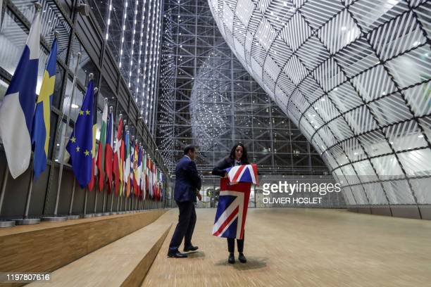EU Council staff members remove the United Kingdom's flag from the European Council building in Brussels on Brexit Day January 31 2020 Britain leaves...