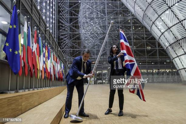 Council staff members remove the United Kingdom's flag from the European Council building in Brussels on Brexit Day January 31 2020 Britain leaves...