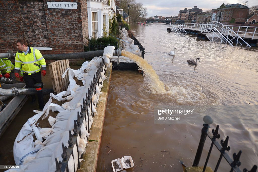 Council woprkers attempt to protect properties with sandbags and pumps next to the River Ouse on November 27,2012 in York,England. Floodwaters threaten hundreds of homes in Wales and England, as river levels continue to rise exacerbated by further water running into already saturated areas.