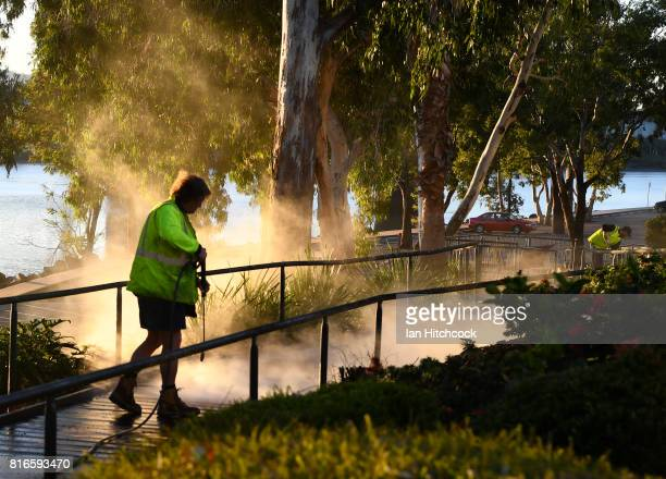 A council worker is seen water blasting a concrete wlkway along the banks of the Fitzroy river on July 12 2017 in Rockhampton Australia
