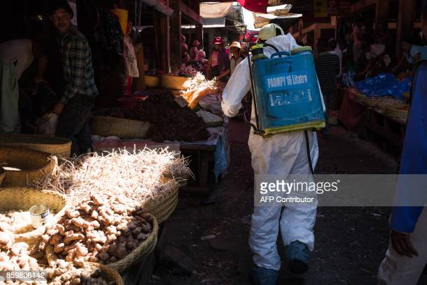 A council worker sprays disinfectant during the cleanup of the market of Anosibe in the Anosibe district one of the most unsalubrious district of...