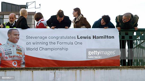 Council workers admire a banner celebrating Lewis Hamilton's F1 2008 World Championship victory in Stevenage in southern England on November 7 2008...
