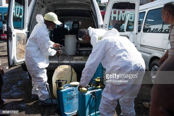 Council workers fill containers as they prepare to spray disinfectant during the cleanup of the market of Anosibe in the Anosibe district one of the...