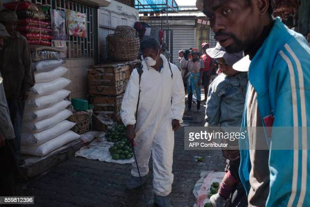 Council workers spray disinfectant as they cleanup the market of Anosibe in the Anosibe district one of the most unsalubrious district of...