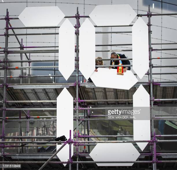Councillor Said Kasmi and Sharon change the countdown clock of the Eurovision Song Contest in Rotterdam, on March 4, 2021. - The clock counts back...