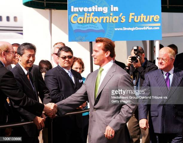 Councilmember-at large Henry Chang and Phil Tagami look on as Governor Arnold Schwarzenegger shakes hands alongside Senator Don Perata at Kaiser Air...