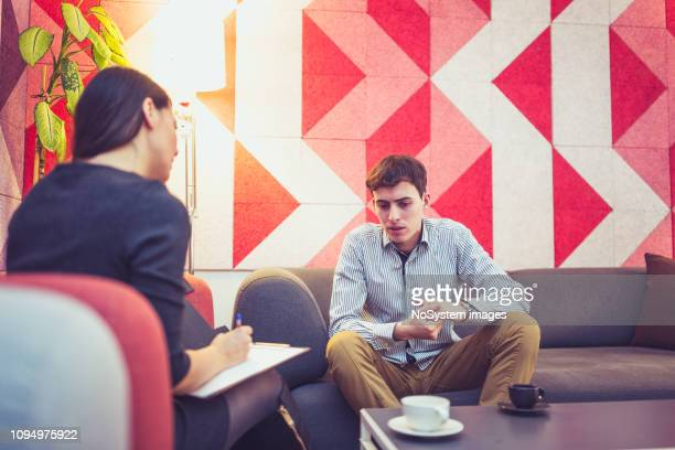 counseling. therapist talking to young man in therapy session - psychiatrist's couch stock pictures, royalty-free photos & images