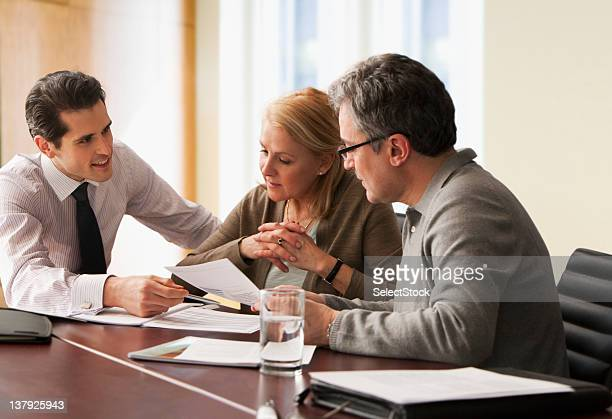 Counselor going over papers with older couple