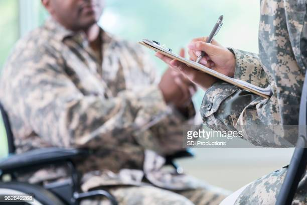 counselor takes notes while talking with injured soldier - injured u.s. army stock photos and pictures