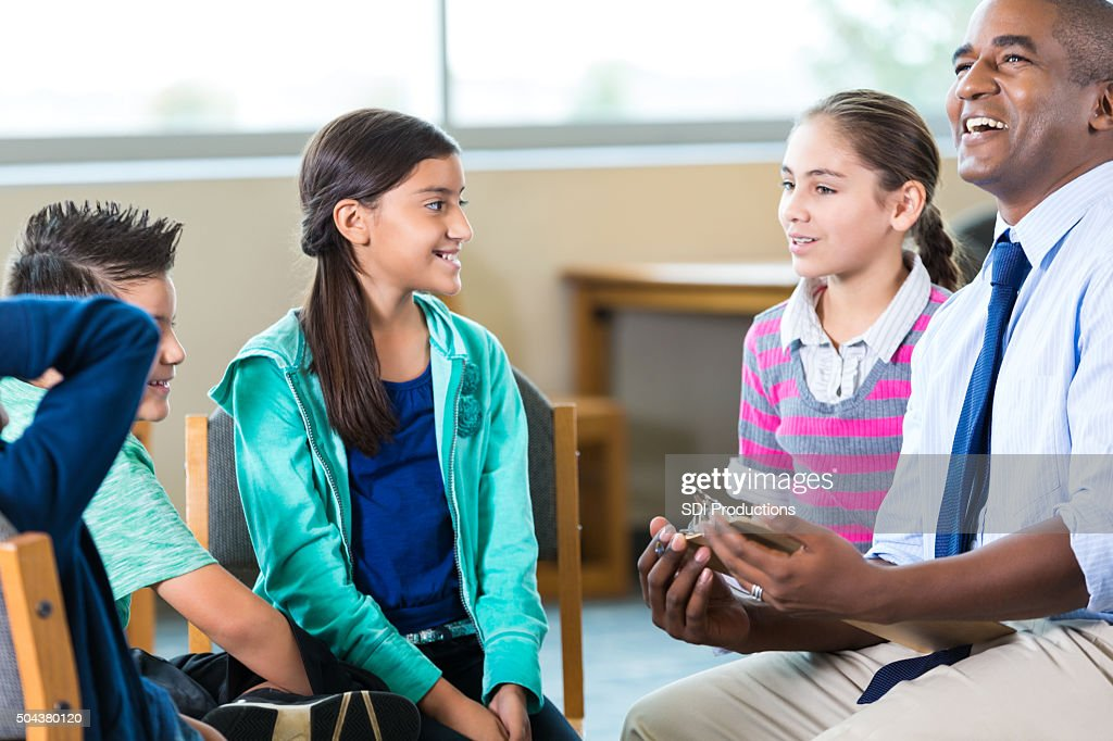 Counselor talking to group of elementary age students : Stock Photo