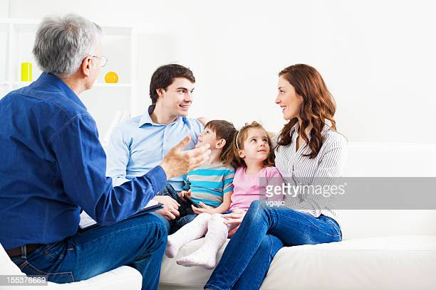 Counselor talking to man, wife and two children