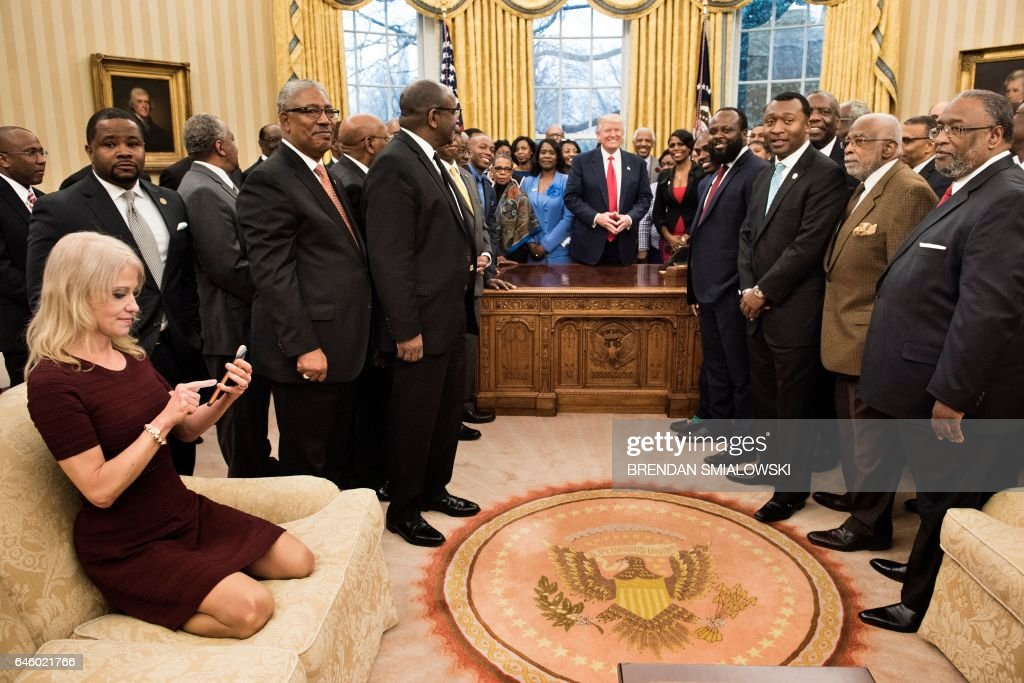 Presidential counselor Kellyanne Conway checks her phone after taking a group photo, with feet casually on the couch, Washington, DC, February 27, 2017.