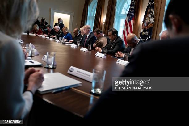 Counselor to the President Kellyanne Conway US President Donald Trump and others bow their heads in prayer during a meeting on border security in the...