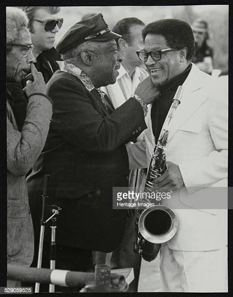 Count Basie chatting with Illinois Jacquet at the Capital Radio Jazz Festival, London, July 1979. Count Basie Orchestra drummer Butch Miles, wearing...