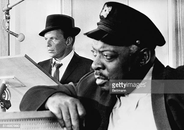 Count Basie leans in the foreground as Frank Sinatra stands at a lectern near a microphone Sinatra worked on arrangements with Basie and toured with...