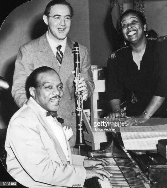 Count Basie plays the piano and Benny Goodman holds his clarinet next to Ethel Waters during a performance at the Stage Door Canteen