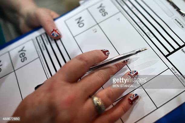 A count observer with Union flag finger nails looks on as ballot papers are counted in the Aberdeen Exhibition and Conference Centre in Aberdeen on...