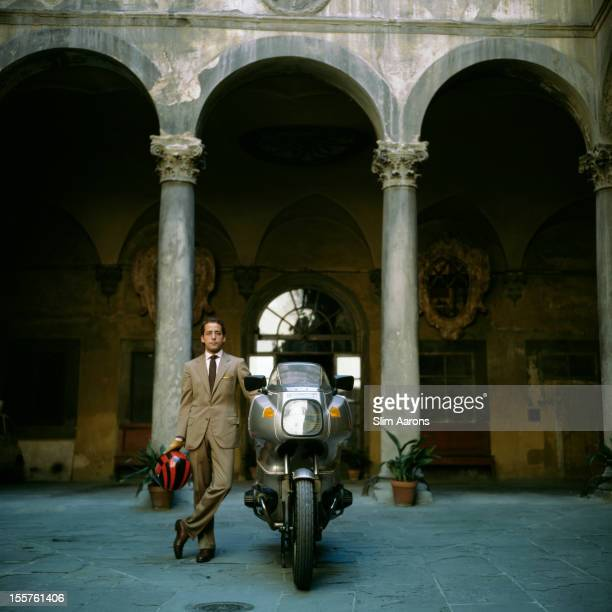 Count Simone Rucellai stands holding a crash helmet while posing beside a motorcycle in Florence Italy 1984