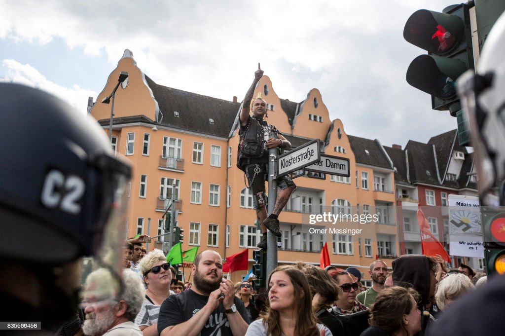 A counter demonstrator gesture and cant slogans towards a gathering of Neo-Nazis (unseen) at the end of their march, on August 19, 2017 in Berlin, Germany. Some 1000 participants affiliated with Neo-Nazi and extreme right groups marched through the street of Berlin's Spandau district in commemoration of 30 years to Rudolf Hess's death, on August 19, 2017 in Berlin, Germany. Hess committed suicide on August 17, 1987 at Spandau Prison and he also served as Adolf Hitler's deputy. The march attracted counter demonstrations along its route, organized by several left-wing groups and political parties.