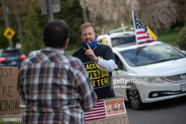 A counter protester agues with a demonstrator at a Rolling Car Rally in front of Democratic Governor Ned Lamont's residence while protesting the...