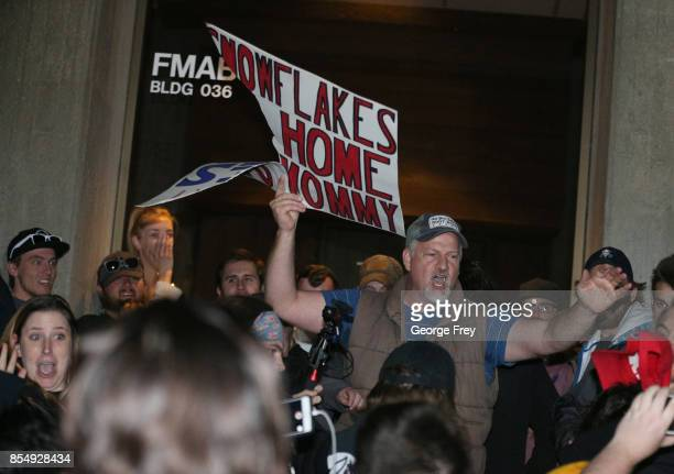 A counter protester shows his ripped sign that was torn by protesters demonstrating on the University of Utah campus against an event where right...