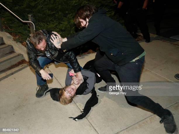 A counter protester takes down a protester after he was allegedly hit by her as another protester pushes him off during a demonstration on the...