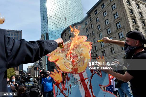 Counter protesters set fire to an effigy of US President Donald Trump during a gathering of the far right group 'Super Fun Happy America' as they...