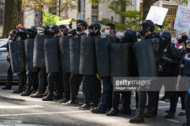 Counter protestors stand with their handmade shields facing police officers that stand between them and supporters of Donald Trump during a 'Stop the...