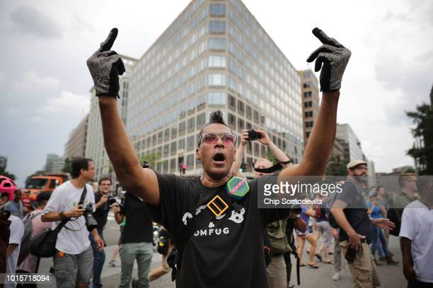 A counterdemonstrator shouts and gestures at participants in the white supremacist Unite the Right rally as they march near White House August 12...