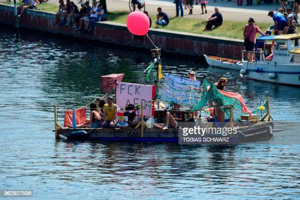 Counterdemonstrators drive on the Spree with a boat in the direction of the main station in Berlin to protest against the 'demonstration for the...