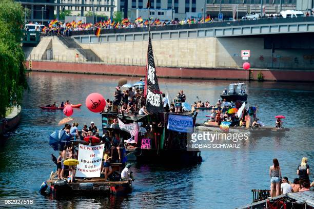 Counterdemonstrators drive on the Spree with boats and rafts in the direction of the main station in Berlin to protest against the 'demonstration for...